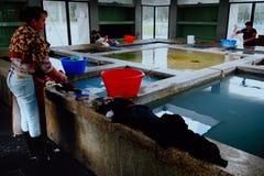 donna locale che lava i panni ad una stanza di lavanderia tradizionale della comunità fotografia stock