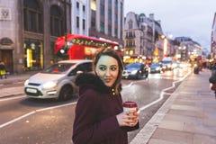Donna a Londra che fa una pausa una strada di grande traffico alla notte immagine stock libera da diritti