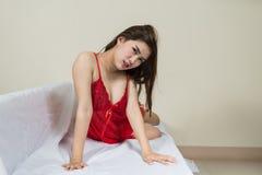 Donna lussuosa della testarossa in un vestito rosso sullo strato bianco immagini stock