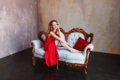 Donna lussuosa della testarossa in un vestito rosso sullo strato classico bianco nell'interno minimalistic del sottotetto fotografie stock