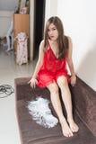 Donna lussuosa della testarossa in un vestito rosso sullo strato marrone immagine stock