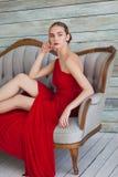 Donna lussuosa in un vestito rosso sullo strato Immagini Stock Libere da Diritti