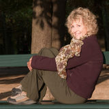 Donna maggiore attraente sul banco Fotografie Stock