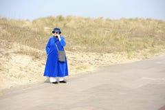 Donna maggiore in azzurro con il telefono delle cellule Immagine Stock