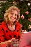 Donna maggiore che acquista in linea per i regali di natale Immagine Stock