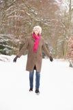 Donna maggiore che cammina attraverso il terreno boscoso dello Snowy Fotografie Stock Libere da Diritti