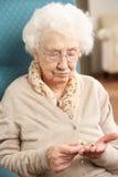 Donna maggiore che esamina farmaco Fotografia Stock Libera da Diritti