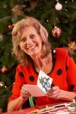 Donna maggiore che fa le cartoline di Natale nel paese Fotografie Stock