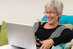 Donna maggiore che lavora ad un computer portatile fotografie stock libere da diritti