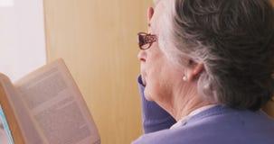 Donna maggiore che legge un romanzo video d archivio