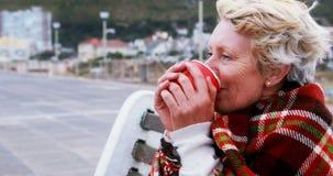 Donna maggiore che mangia caffè video d archivio