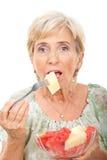 Donna maggiore che mangia l'insalata dei meloni Immagine Stock