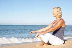 Donna maggiore che Meditating sulla spiaggia fotografie stock libere da diritti