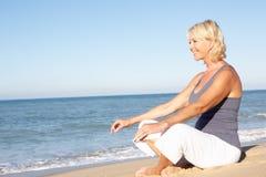 Donna maggiore che Meditating sulla spiaggia fotografia stock