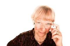 Donna maggiore che osserva sopra i suoi vetri Fotografia Stock Libera da Diritti