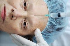 Donna maggiore che ottiene l'iniezione del botox Fotografie Stock Libere da Diritti
