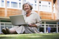 Donna maggiore che per mezzo del computer portatile sulla città universitaria Fotografie Stock