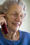 Donna maggiore che per mezzo del telefono delle cellule Fotografie Stock Libere da Diritti