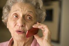 Donna maggiore che per mezzo del telefono delle cellule Immagine Stock
