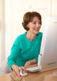 Donna maggiore che per mezzo felicemente del calcolatore Immagine Stock