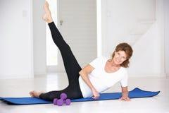 Donna maggiore che risolve in ginnastica domestica Fotografia Stock
