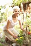 Donna maggiore che si distende nel giardino fotografie stock