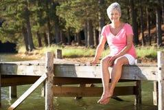 Donna maggiore che si siede dal lago immagine stock
