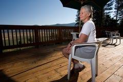 Donna maggiore che si siede dal raggruppamento fotografia stock libera da diritti