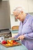 Donna maggiore che taglia le verdure a pezzi in cucina Fotografie Stock Libere da Diritti