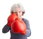 Donna maggiore con i guanti di inscatolamento Fotografia Stock