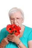 Donna maggiore con i papaveri rossi artificiali Immagini Stock