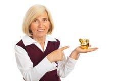 Donna maggiore felice che indica la banca piggy Fotografie Stock Libere da Diritti