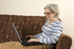 Donna maggiore felice che per mezzo del computer portatile Immagini Stock