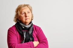 Donna maggiore nel colore rosa con le braccia attraversate Immagini Stock