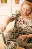 Donna maggiore sorridente con il kit di cucito Immagini Stock