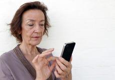Donna maggiore Texting immagine stock
