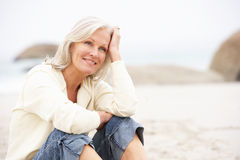Donna maggiore in vacanza che si siede sulla spiaggia di inverno Fotografia Stock