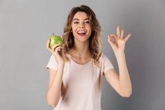Donna in maglietta che fora mela fresca e che mostra segno giusto Immagini Stock