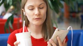 Donna in maglietta rossa che si siede in caffè facendo uso del suo smartphone, cola bevente d'ascolto di musica dalla tazza di ca