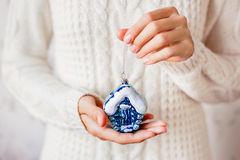 Donna in maglione che tiene una decorazione di natale - casa blu Fotografia Stock