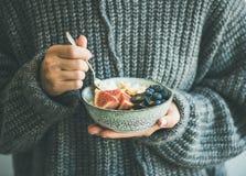 Donna in maglione di lana grigio che mangia il porridge della noce di cocco del riso Fotografia Stock Libera da Diritti