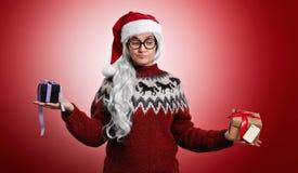 Donna in maglione di Natale e cappello di Santa con i presente fotografie stock libere da diritti