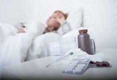 Donna malata che ritiene cattiva menzogne malata sul virus di sofferenza di freddo e di influenza di inverno di emicrania del let Fotografia Stock