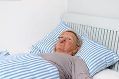 Donna malata che si trova sul letto con il termometro in bocca Fotografia Stock
