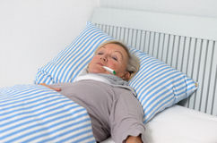 Donna malata che si trova sul letto con il termometro in bocca Immagini Stock Libere da Diritti