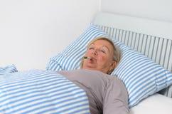 Donna malata che si trova sul letto con il termometro in bocca Fotografia Stock Libera da Diritti