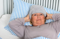 Donna malata che si trova sul letto con l'asciugamano sulla fronte Fotografie Stock