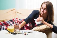 Donna malata che si trova sul sofà sotto il naso di starnuto della lana e di pulitura generale Freddo preso immagine stock