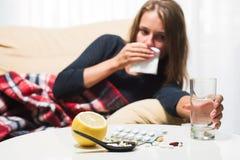 Donna malata che si trova sul sofà sotto il naso di starnuto della lana e di pulitura generale Freddo preso Fotografia Stock