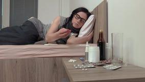 Donna malata che si trova sulla pillola della presa e del letto archivi video
